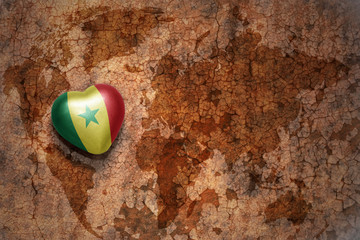 heart with national flag of senegal on a vintage world map crack paper background.