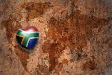 heart with national flag of south africa on a vintage world map crack paper background.