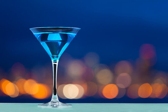 Glass of martini standing against city lights