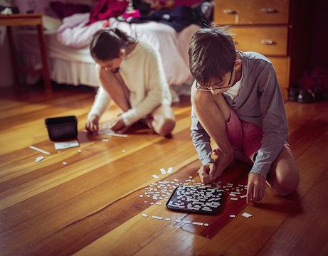 Mixed race children doing puzzles on bedroom floor