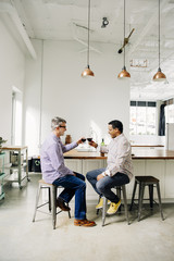 Gay couple toasting with wine at counter