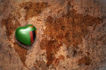 heart with national flag of zambia on a vintage world map crack paper background.