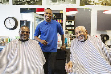 Black barber and customers smiling in retro barbershop