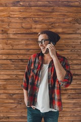 Hipster young man in hat and glasses talking on phone