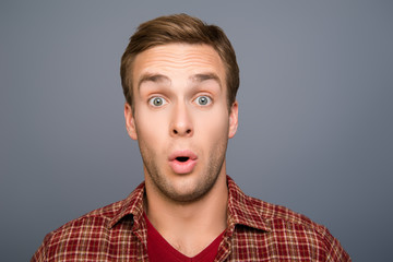 Portrait of handsome young shocked man with open mouth