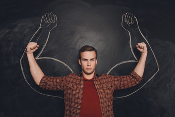 Young man against the background of depicted muscles on chalkboa