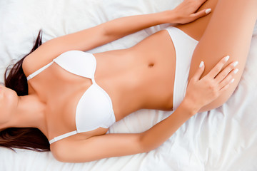 Close up photo of girl with a beautiful figure lying on the bed