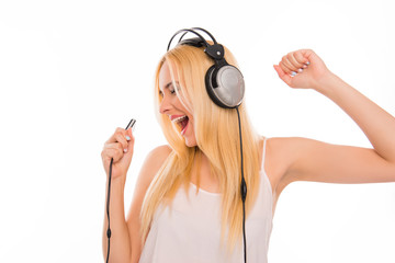 Cheerful lady with mp3 and headphones listening music and singin