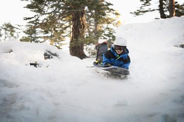 Mixed race boy sledding on snowy hillside