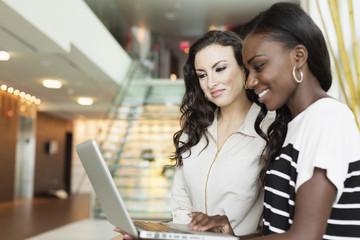 Businesswomen using laptop in hotel lobby