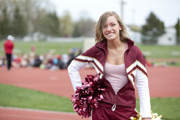 Caucasian cheerleader smiling on track