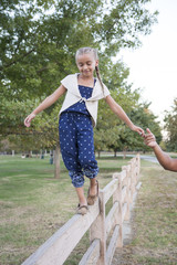 Father helping daughter balance on wooden fence