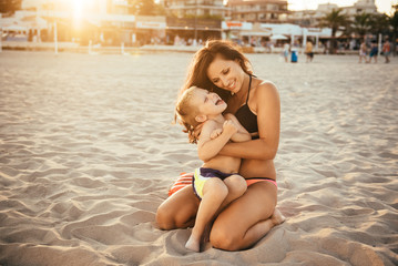 Portrait of a young single mother spending time with her son during holidays at the seaside. Woman touching her son with care, playing and hugging.