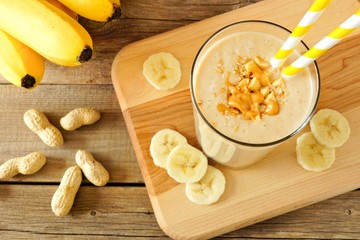Peanut butter banana oat smoothie with paper straws, on a wood board on rustic table, downward view