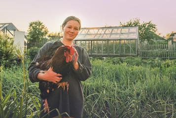 Caucasian farmer holding chicken in garden
