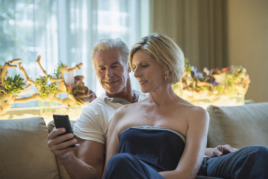 Caucasian couple using cell phone in hotel lobby