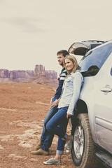 Caucasian couple at car admiring Monument Valley, Utah, United States