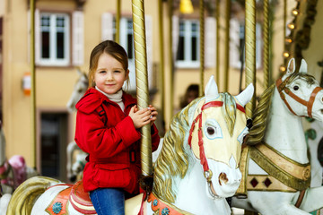 Little girl sitting on carousel horse