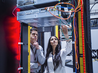 Technicians examining computer in server room