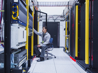 Hispanic technician examining computer in server room