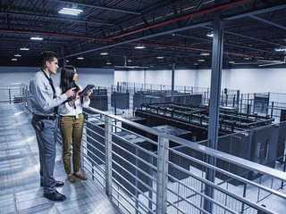 Business people examining server room from balcony