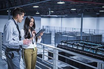 Business people using digital tablet over server room