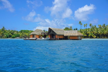 Tropical home with thatch roof over water with the shore of an islet in background, Huahine island, Pacific ocean, French Polynesia