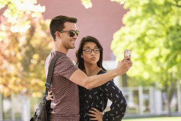 Students taking cell phone photograph on college campus