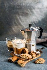Glass of latte coffee on rustic wooden board, cantucci biscuits and steel Italian Moka pot, grey background