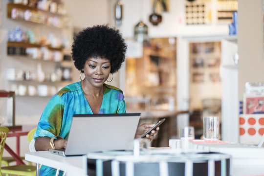 Female business owner using laptop in store