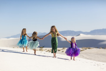 Girls walking on desert sand dunes