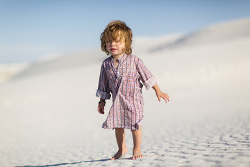 Caucasian baby boy walking on desert sand dune