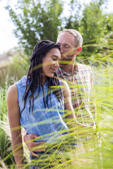 Couple kissing in tall grass in garden