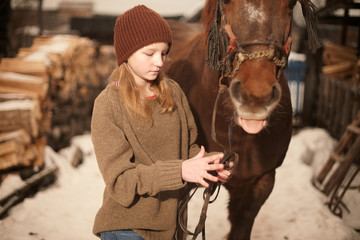 Caucasian teenage girl leading horse in snowy field
