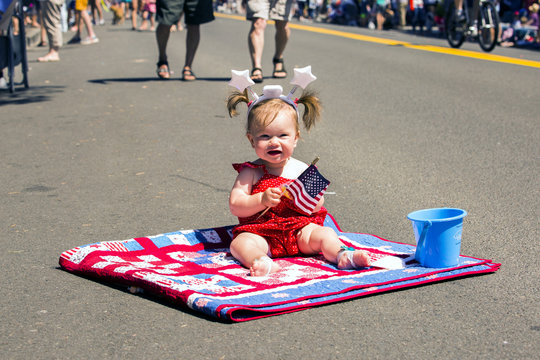 Caucasian girl sitting on quit at 4th of July parade