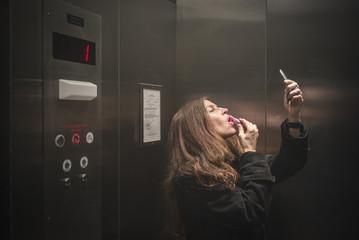 Caucasian woman applying lipstick in elevator