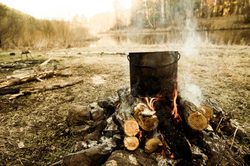 Pot cooking on campfire in rural field