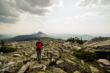 Caucasian hiker walking in rocky field in remote landscape