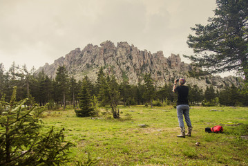 Caucasian hiker photographing mountain in remote landscape