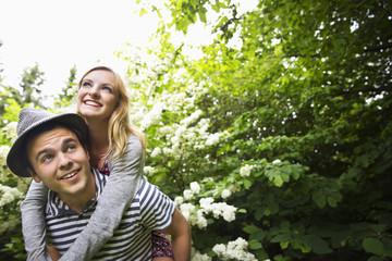 Caucasian man carrying girlfriend piggyback in garden