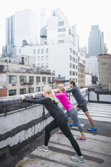 Caucasian athletes stretching on urban rooftop