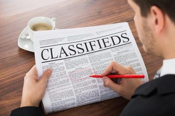 Businessman Highlighting Advertisement On Newspaper