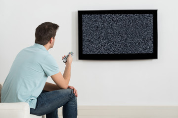 Man Sitting On Sofa In Front Of Television