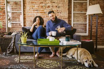 Couple enjoying breakfast on sofa in living room