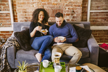 Couple eating breakfast on sofa in living room