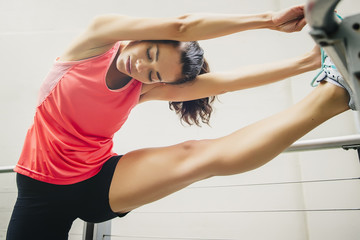 Mixed race athlete stretching on banister