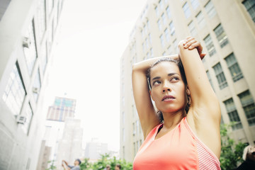 Mixed race athlete stretching in city