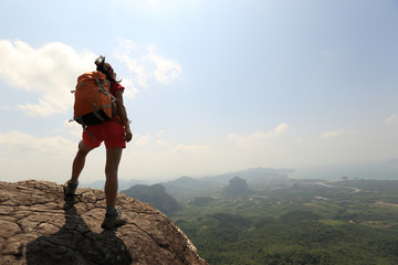 young successful woman backpacker on mountain peak