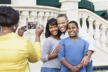 African American woman taking cell phone photograph of family