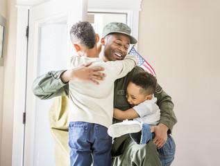 Returning soldier hugging children at door